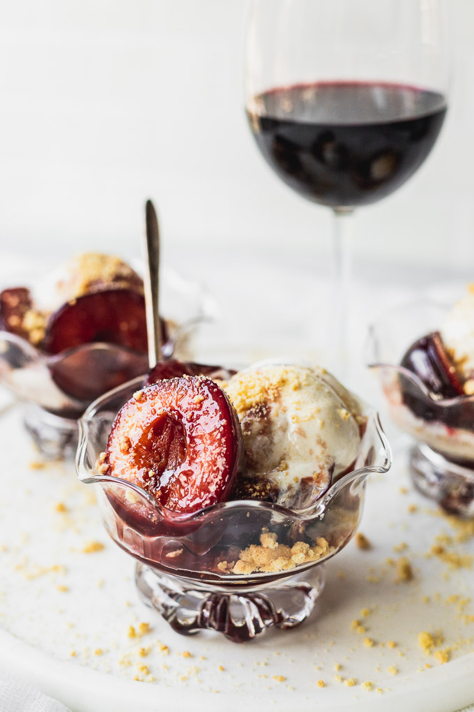 bowl of sauteed fresh plum dessert with ice cream and wine sauce with spoon
