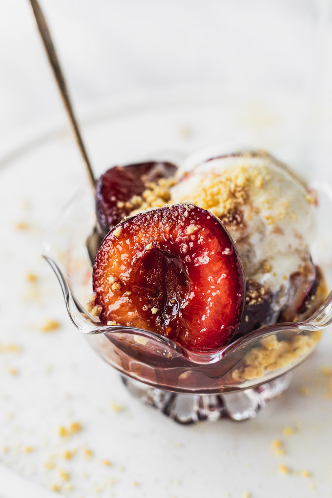 sauteed plums in bowl with ice cream and spoon