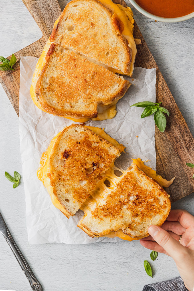 hand pulling grilled cheese slice