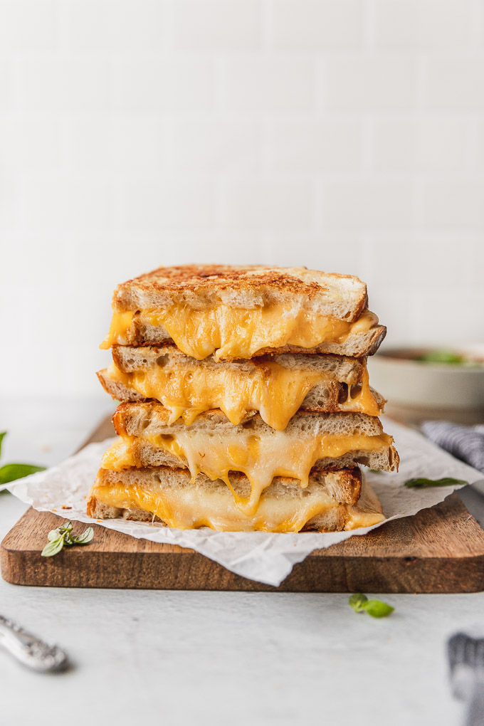 stack of grilled cheese sandwiches with cheese oozing