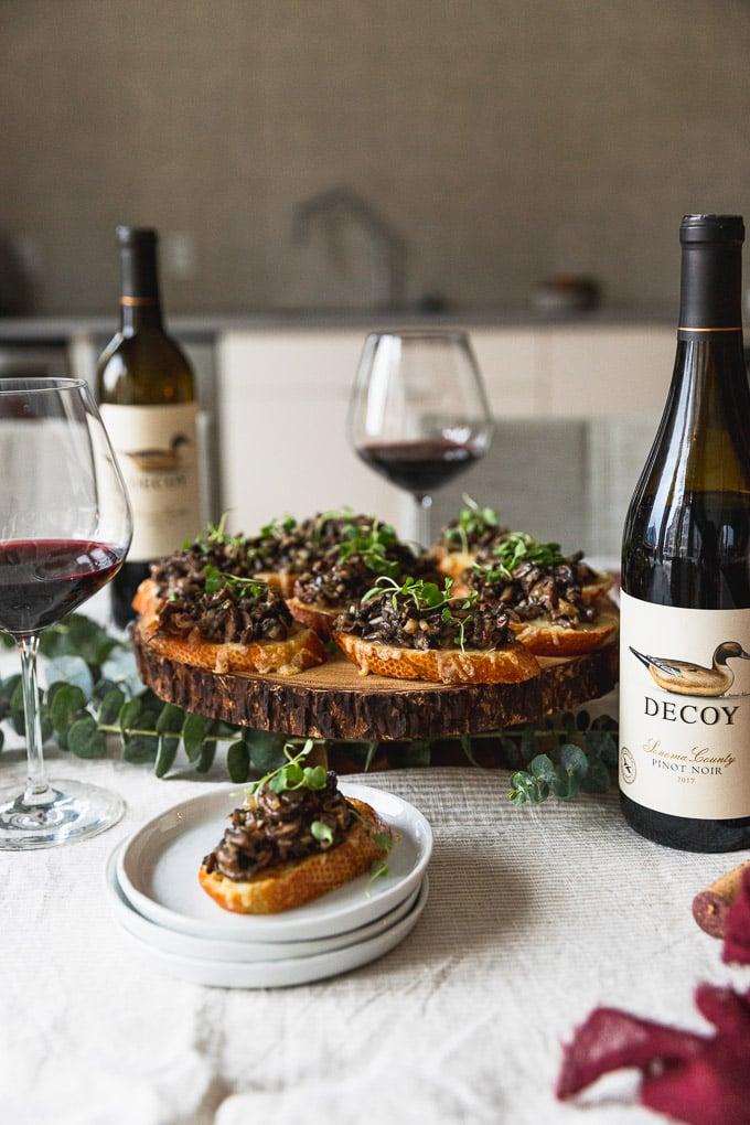 platter of mushroom bruschetta next to a bottle of wine and wine glasses