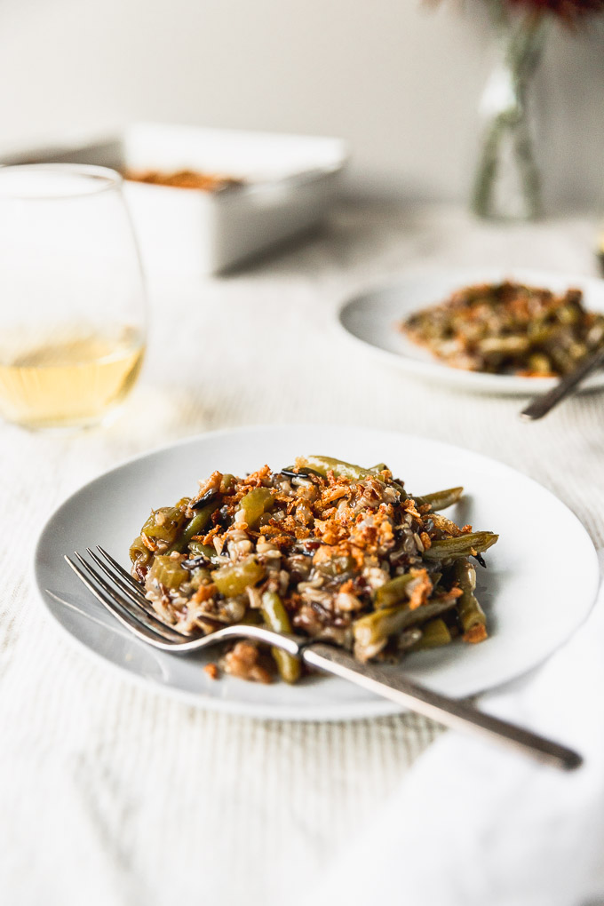 white plate with a serving of green bean casserole with fork next to it and a glass of wine
