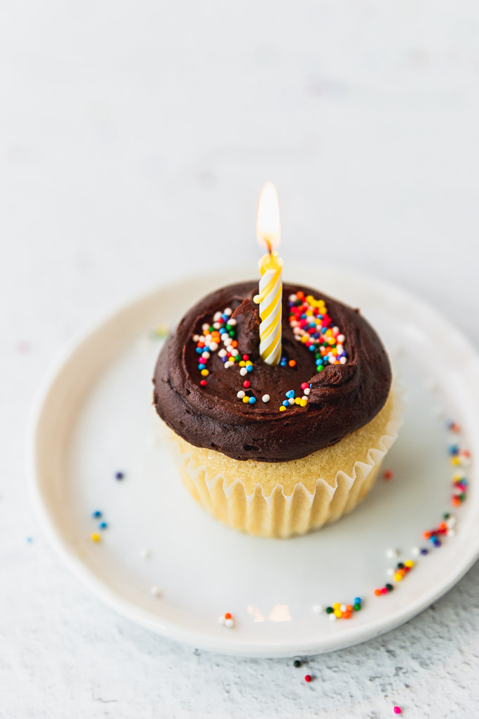 yellow cupcake with chocolate buttercream with lit candle on white plate with sprinkles