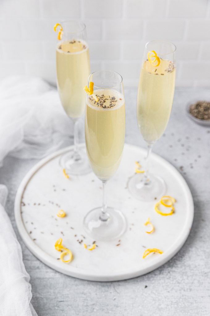 three champagne glasses with lavender and lemon twist