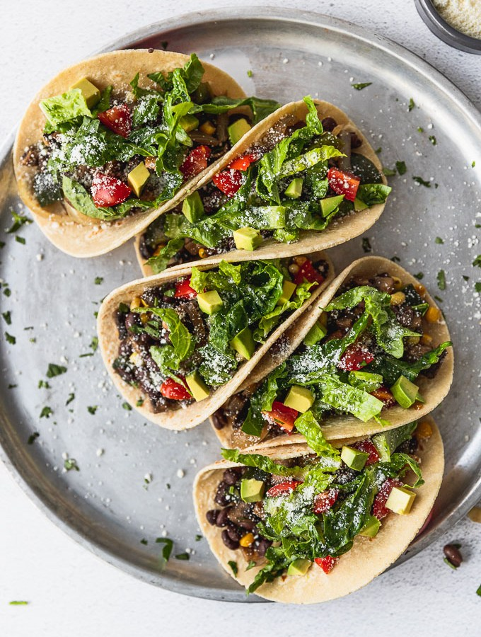 overhead view of five tacos with lettuce on top on silver tray