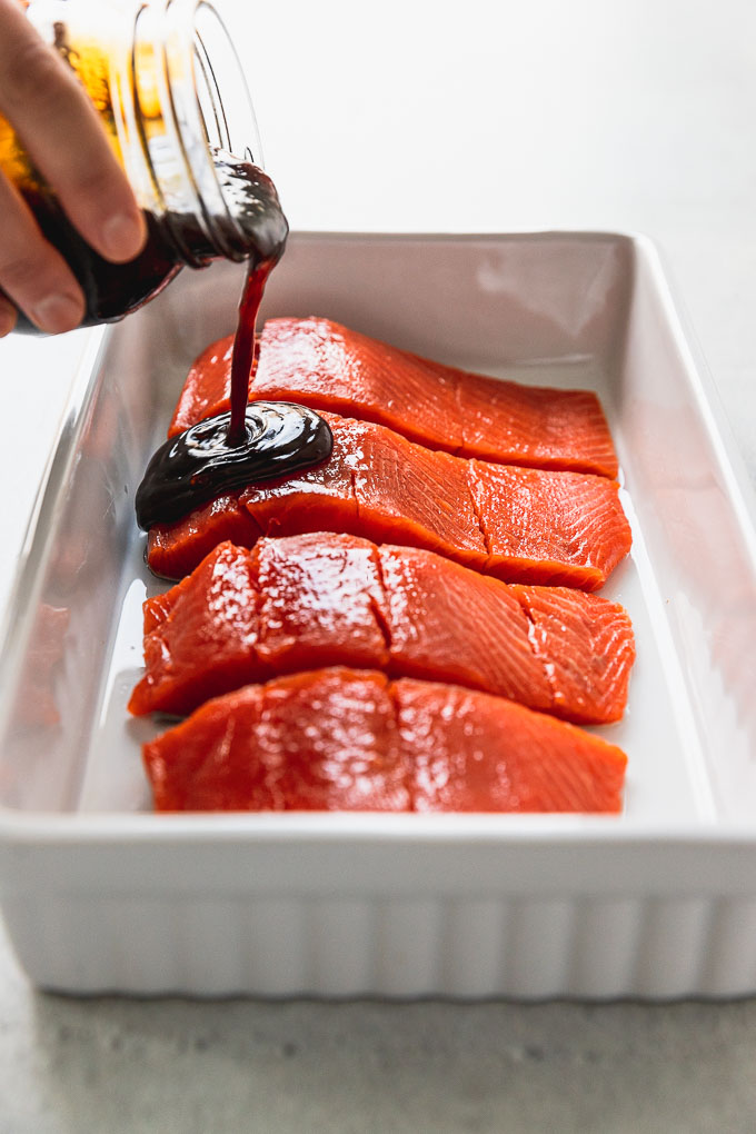 pouring teriyaki sauce on salmon filets in white baking dish