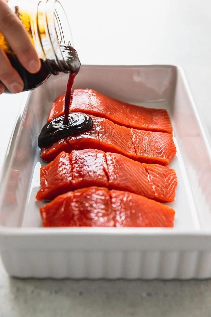 pouring teriyaki sauce on salmon filets in white baking dish
