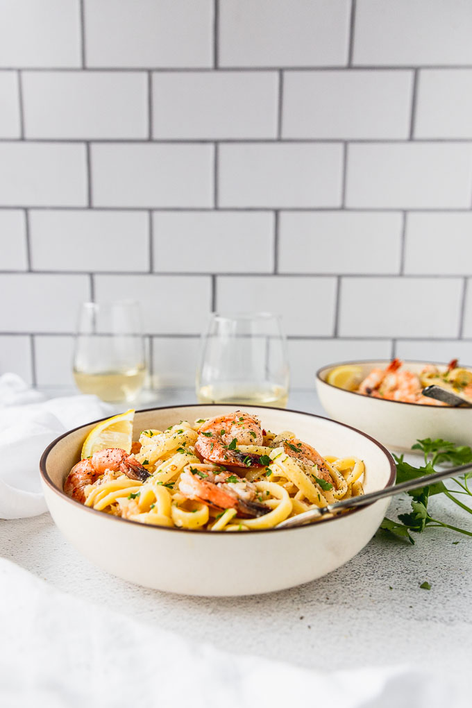 two bowls of shrimp scampi pasta with white wine glasses and fork next to