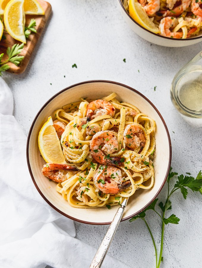 two bowls of shrimp scampi next to board of lemon and parsley