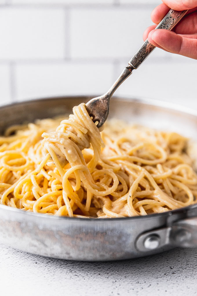 fork twirling spaghetti pasta in large skillet