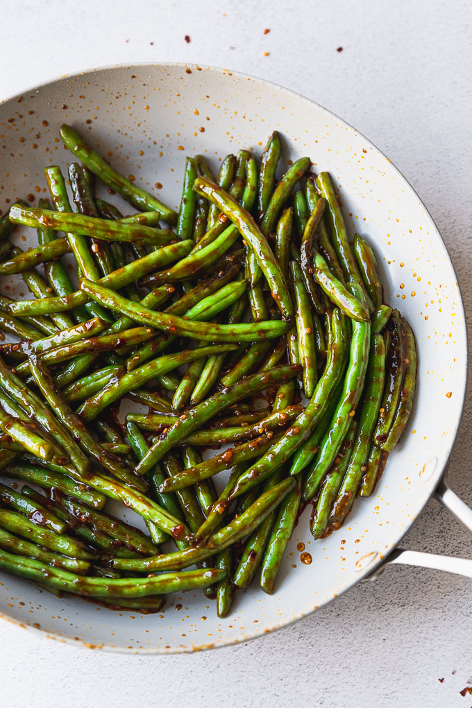 spicy asian green beans in skillet with sauce
