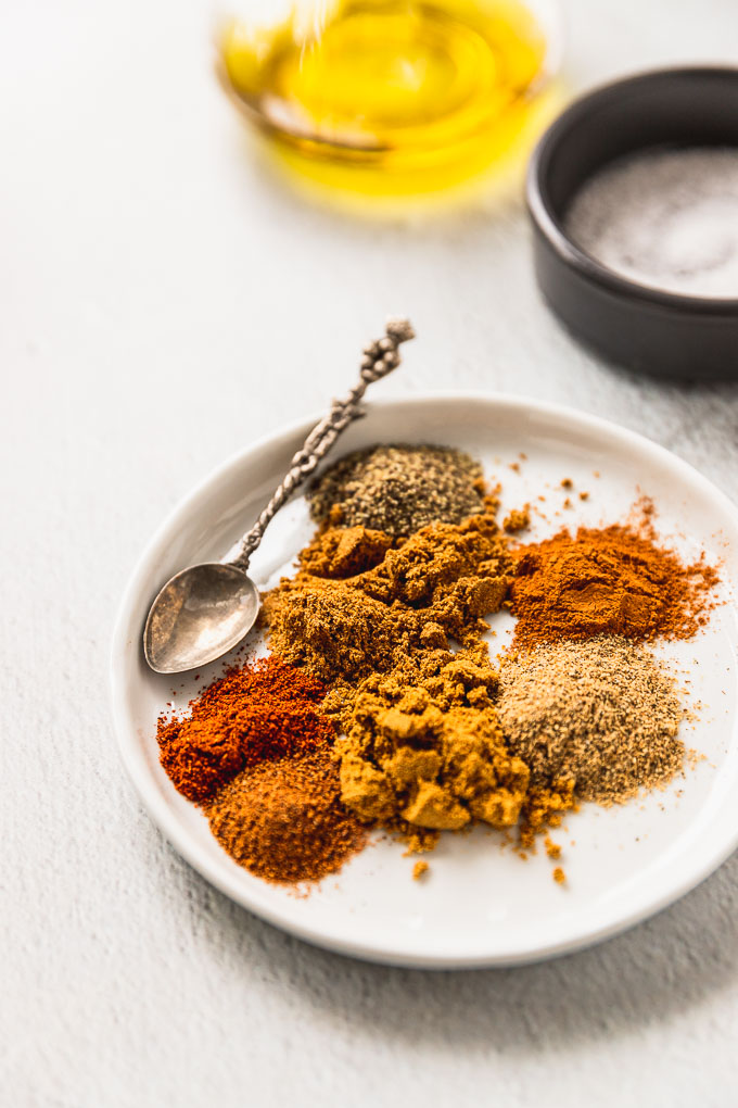 small white plate with many orange, red, and yellow spices with a little spoon next to a gray bowl of salt
