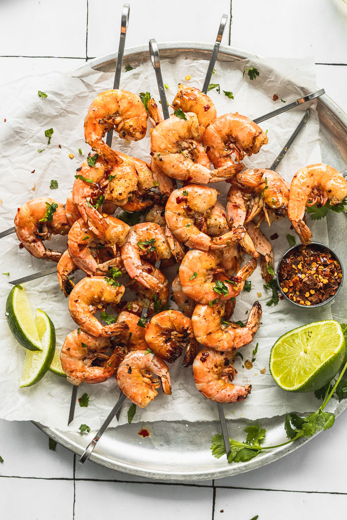 overhead view of skewers on top of each other on a tray in diagonal directions with shrimp next to lime wedges and cup of red pepper flakes