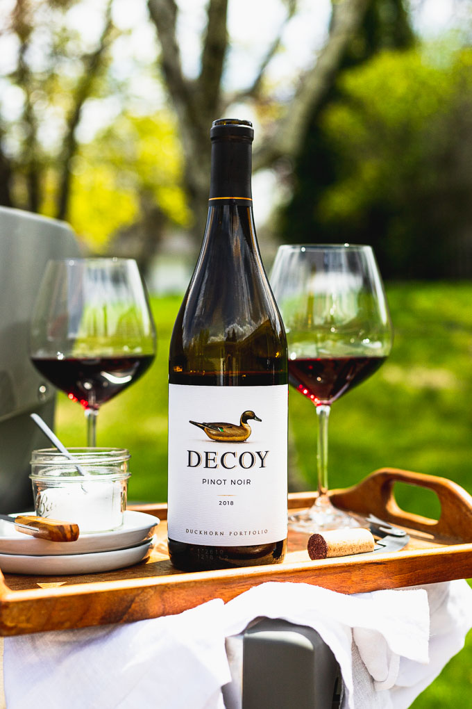 bottle of Decoy wine on a wooden serving tray next to two glasses of red wine, white plates, and a mini bowl of salt with a spoon