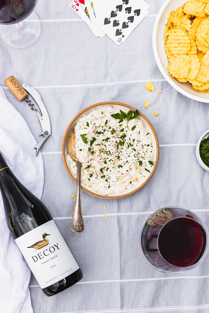 overhead view of bowl of grilled sour cream and onion dip with spoon inside next to a bottle of red wine, two red wine glasses, and potato chips