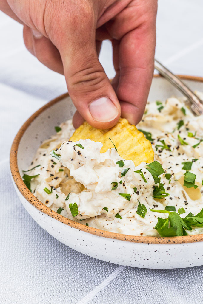 hand dipping chip into a bowl of onion dip