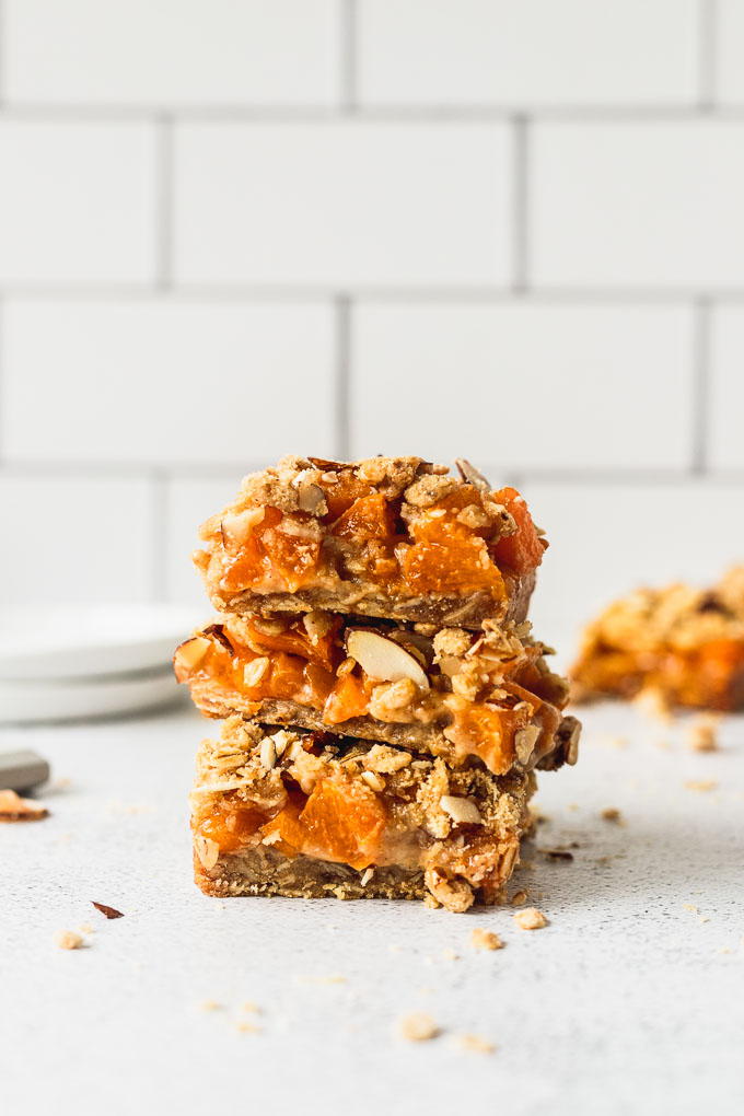 three almond crumble bars stacked on each other with white subway tile in background