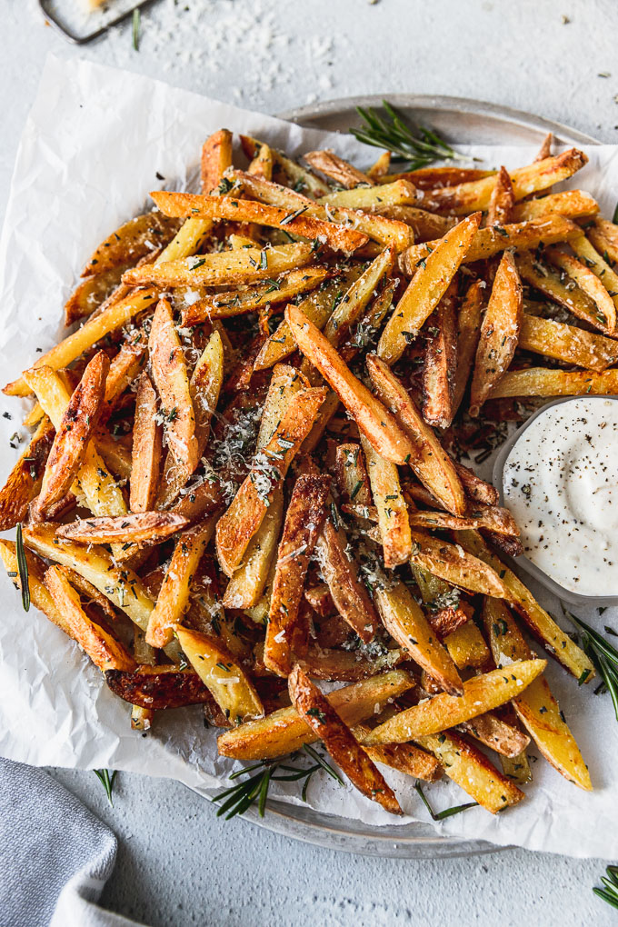 Crispy Baked Rosemary Garlic Parmesan Fries on a tray with parchment paper next to a small bowl of dipping sauce