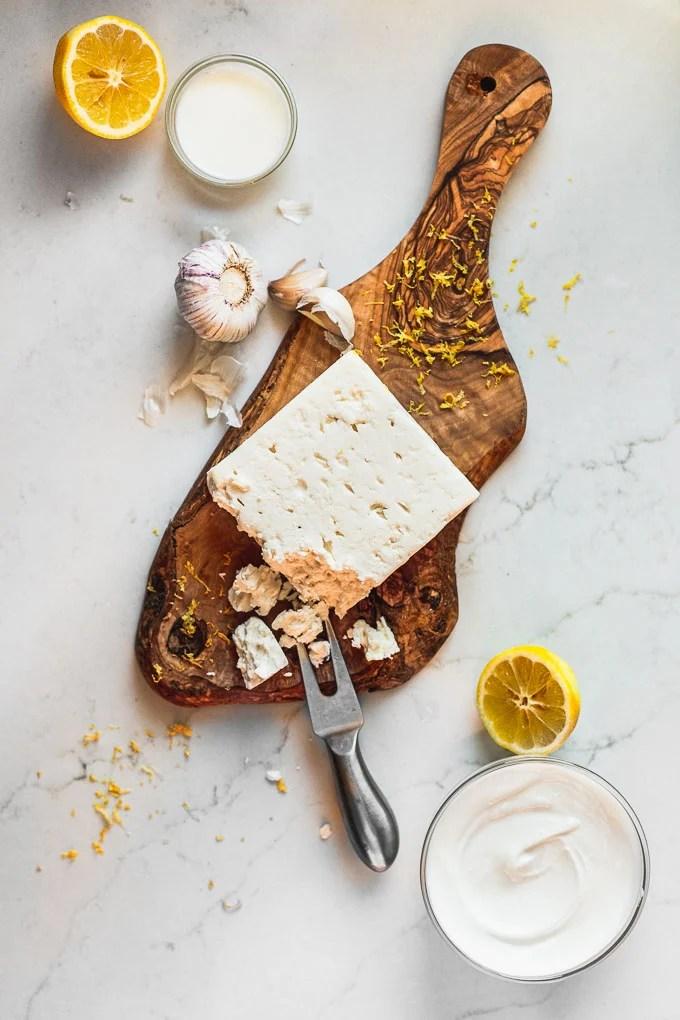 feta block on wood tray with garlic, lemon, and yogurt