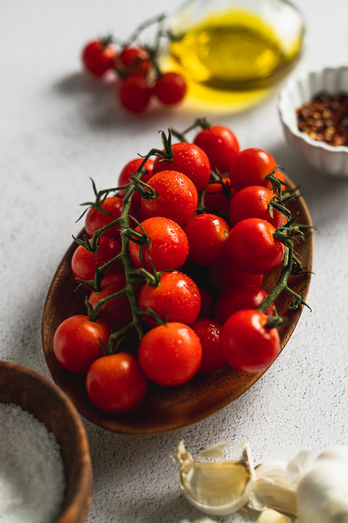 cherry tomatoes on wood server next to red pepper flakes, olive oil, and salt