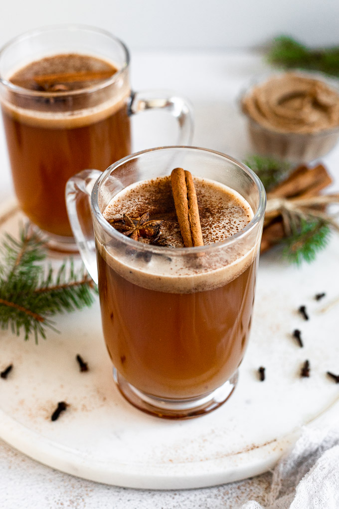 mug of hot buttered rum next to greenery and cinnamon sticks