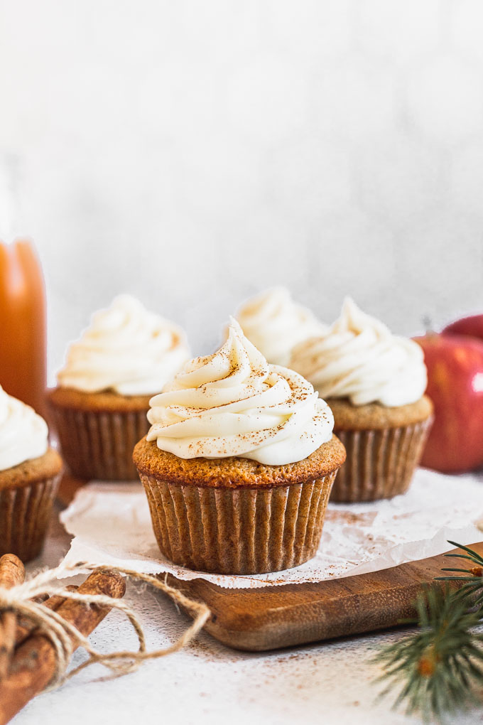 apple cider cupcake on wood board next to apple and cinnamon sticks