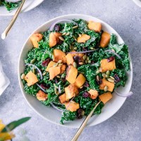 A green kale salad with orange squash with cranberries and pumpkin seeds