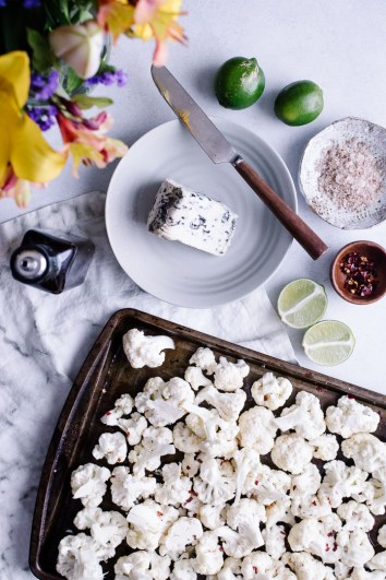 Cauliflower on a pan before roasting with a side of blue cheese, limes, and salt.