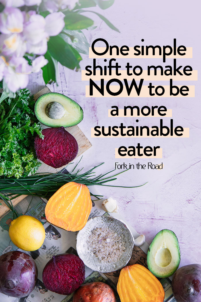"""Vegetables on a pink table with the words """"one simple shift to make now to a be a more sustainable eater"""""""