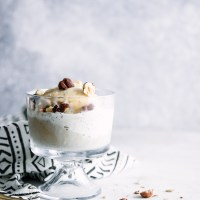 A glass dessert dish with affogato, made with gelato, espresso, and hazelnuts.