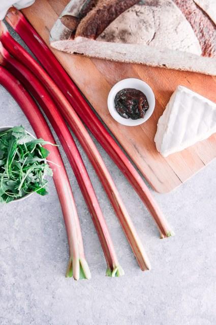 Rhubarb, brie, arugula, jam, and bread on a wooden cutting board.