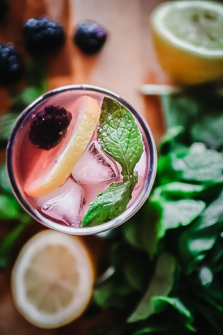 A glass of boozy blackberry lemonade on a cutting board with fresh fruit.