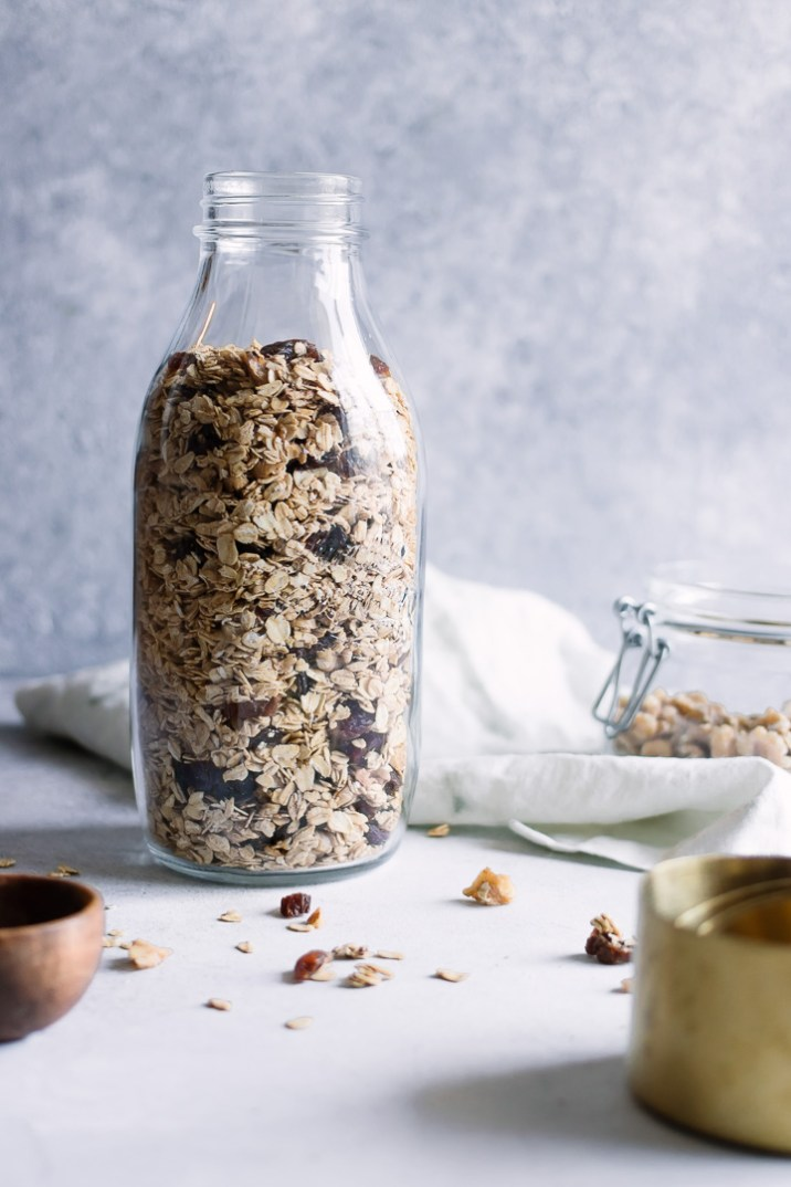 A large mason jar with toasted granola on a white table.