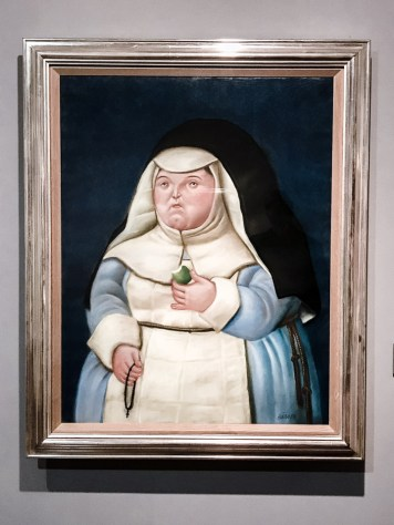 A Botero painting of a nun hanging on a wall.