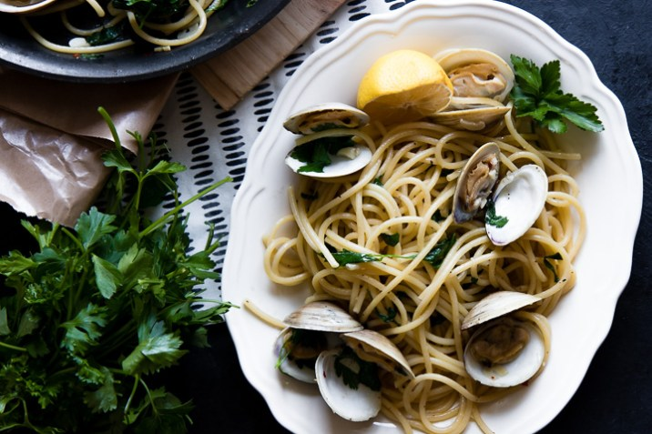 Pasta with clams on a white plate on a black table next to a bunch of parley.