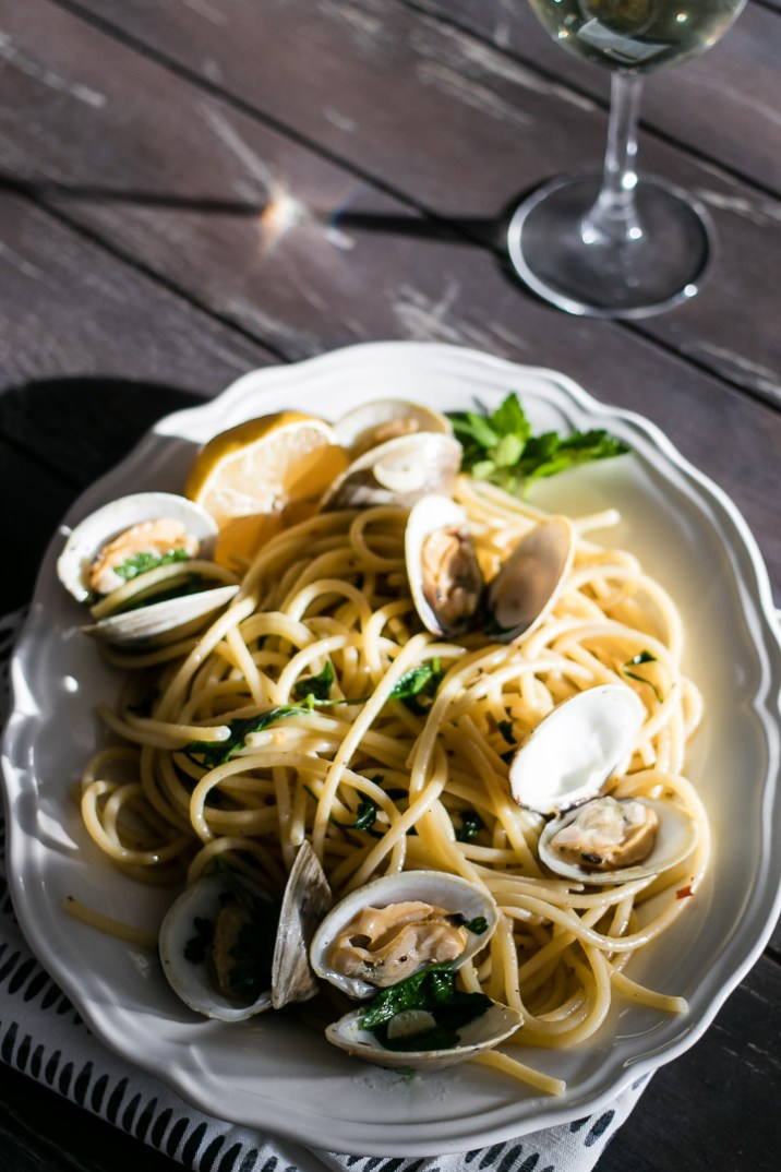 Pasta witch clams on a wood table with a glass of white wine.