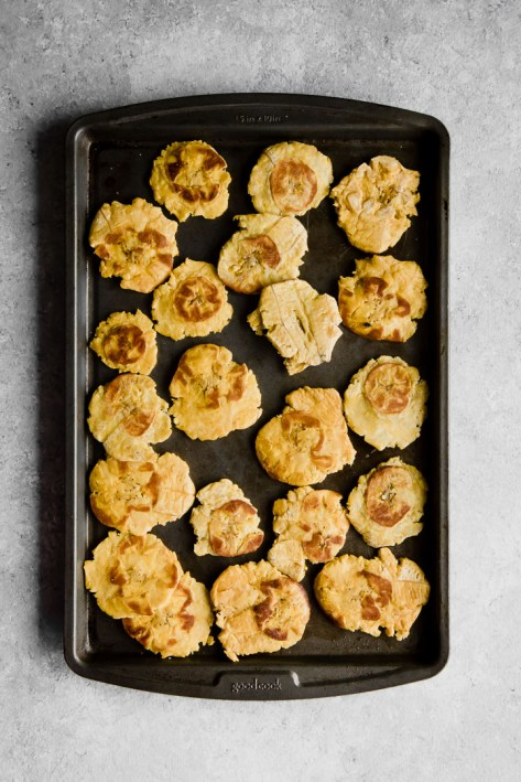 healthy baked patacones, or smashed plantains, on a black cookie sheet