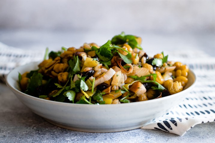 A bowl of za'atar crispy chickpea and leek salad on a blue table.