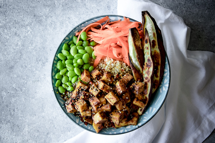Ginger Soy Tofu Bowl recipe in a blue bowl on a grey table.