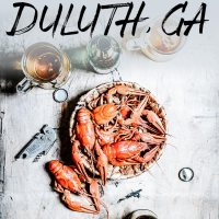 A bowl of crawfish on a while table with a beer at a crawfish boil with the words 5 Foodie Things to do in Duluth, Georgia on top.