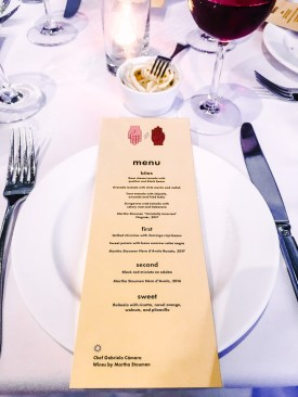 An orange menu on a white place setting on a table.