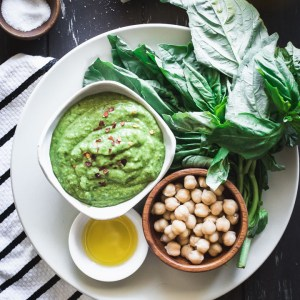 Nut-free chickpea basil pesto on a white plate on a wooden table with a napkin.