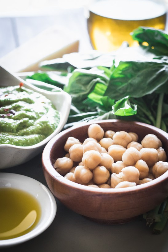 Nut-free basil pesto with chickpeas on a white plate on a wooden table with a napkin.