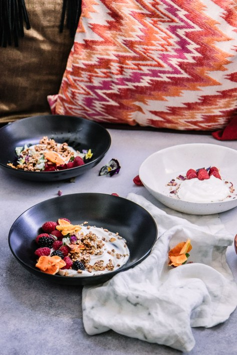 Three bowls with yogurt on a board with red pillows.