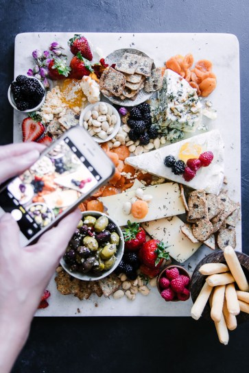 A person taking a photo of a large cheese plate.