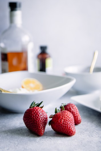 Strawberries on a blue table with with plates in the background.