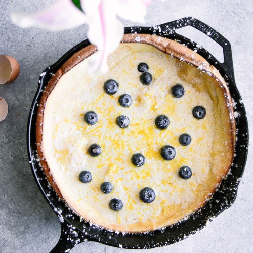 Dutch baby pancake with blueberries in a cast iron skillet on a blue table with pink flowers.