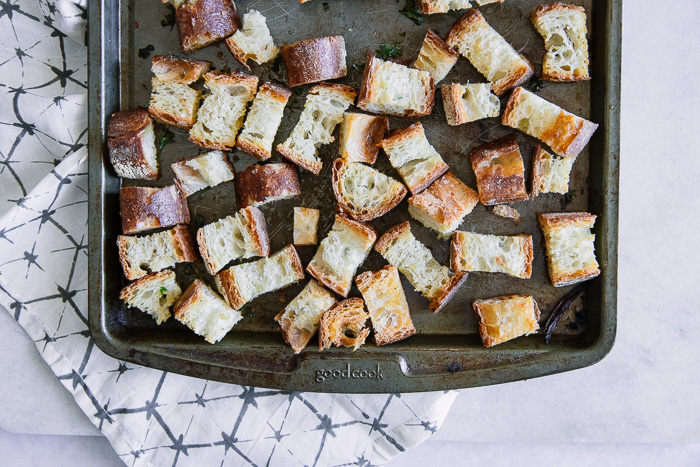 Homemade baked croutons on a metal baking sheet on a white table.