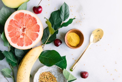 Yellow superfoods on a marble table, including bananas, bee pollen, turmeric, mangos, and grapefruit.