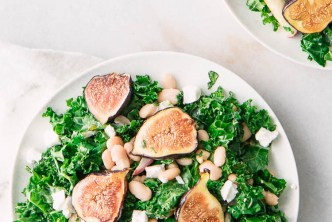 Two white salad plates on a white table with kale, figs, goat cheese, and white beans in a maple dressing.
